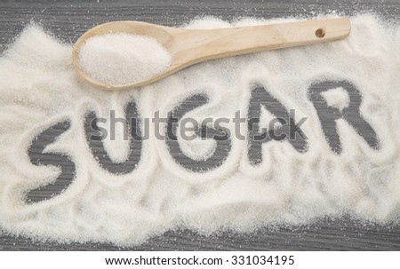 Inscription sugar made into pile of white granulated sugar - stock photo