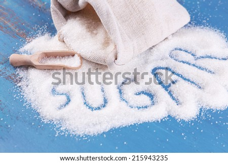 Inscription sugar made of white granulated sugar on color wooden background - stock photo