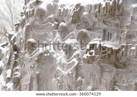 """Inscription """"They were mere mortals"""", a fragment of a bas-relief of """"Wall ruins"""" on Mamayev Kurgan in Volgograd - stock photo"""