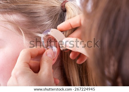 Inserting a hearing aid into a young girl's ear - stock photo