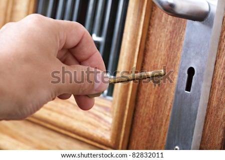 Inserting a key into a house front door - stock photo
