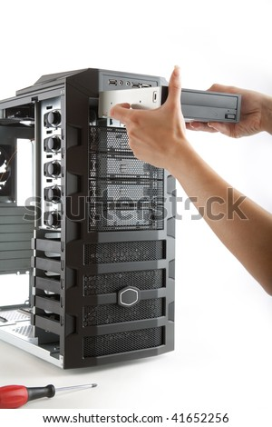 Inserting CD/DVD player in to bare computer case, assembling of a new PC - stock photo