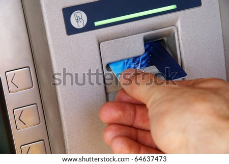 Inserting credit card into bank machine to withdraw money. - stock photo