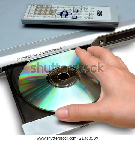 inserting disc to DVD player - stock photo