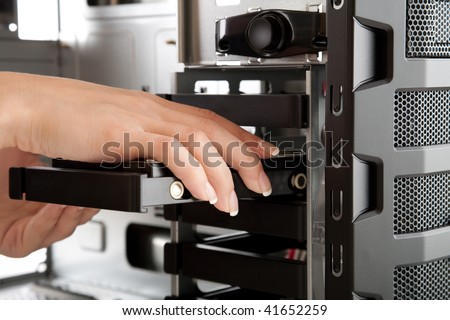 Inserting Hard drive in to bare computer case, assembling of a new PC - stock photo