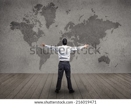 Inside a drab room a man opens his arms in triumph - stock photo