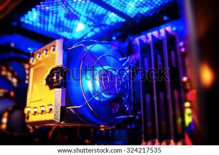 Inside a high performance computer. Computer circuit board and CPU cooling fans illuminated by internal LEDs inside a server class hardware. - stock photo