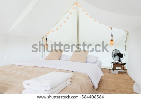 inside a large white tent camp with bed and interior furnishings