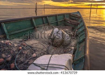 Inside and close up the fisherman boat with fishing net during morning sunrise. - stock photo