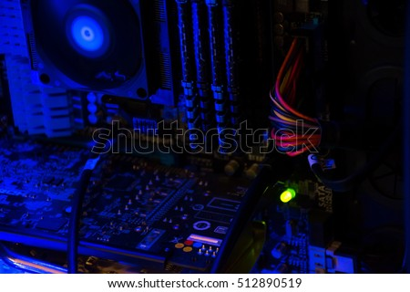 Inside Computer with blue neon glowing light around CPU , RAM , and Video Car with wires and system inside showing as the Computer pushes out information