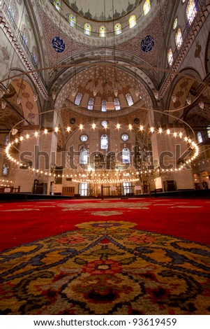 Inside Istanbul Mosque with red carpet in foreground . Picture with a lot of mosque details and big columns - stock photo