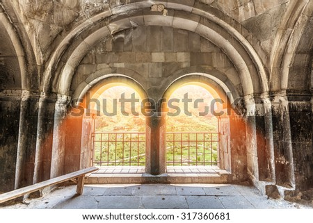 Inside medieval Georgian building with sunlight and green grass outside - stock photo