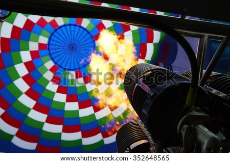 Inside of a colorful hot air balloon as it is inflated for flight, burning burner - stock photo
