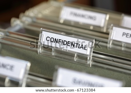 Inside of a filing cabinet with green folders and focus on confidential label - stock photo