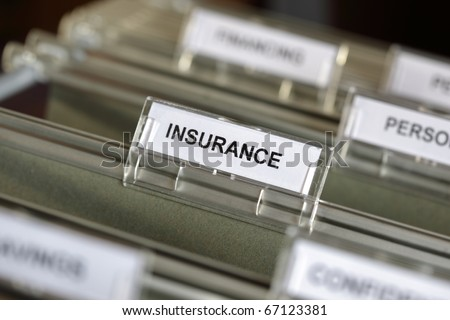 Inside of a filing cabinet with green folders and focus on insurance label - stock photo