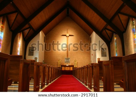 Inside of a large, modern church with pews and cross visible - stock photo