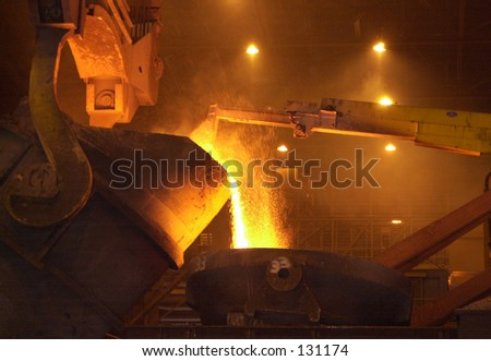 Inside of a steel mill, hot metal pouring. - stock photo