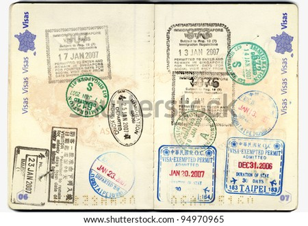 Inside of a well traveled european passport with all kinds of travel stamps from different customs: taipei, china, thailand, hongkong, america - stock photo