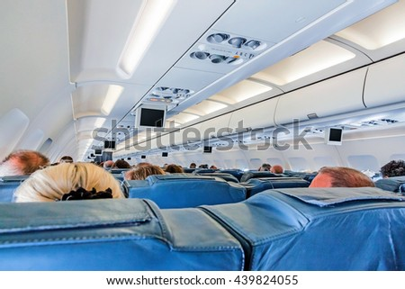 Inside of an airplane cabin - passenger seats during flight - rows with passengers heads from behind.