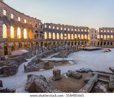 Inside of Ancient Roman Amphitheater in Pula, Croatia, Famous Travel Destination, in Sunny Summer Evening - stock photo