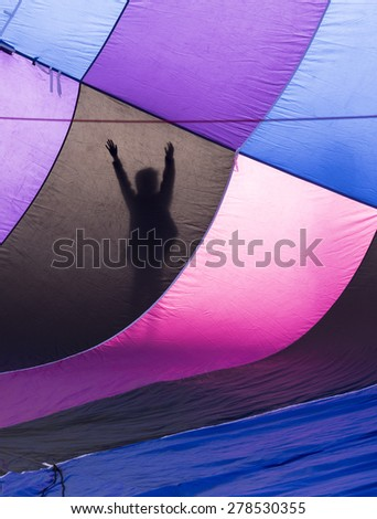 Inside of hot air balloon with silhouette of person - stock photo