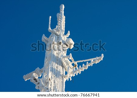 Inside perspective of a tall communications tower in snow day - stock photo