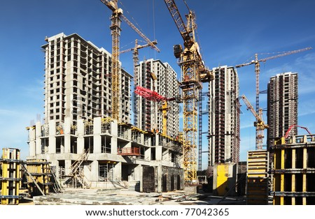 Inside place for many tall buildings under construction and cranes under a blue sky - stock photo