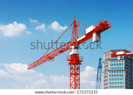 Inside place for tall buildings under construction and cranes under a blue sky - stock photo