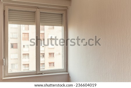 Inside room, view through window showing building.