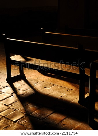Inside shadow detail of church pew with window light - stock photo