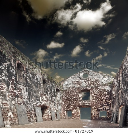 Inside the ancient ruin of St. Paul Church in Melaka, Malaysia with antique tombstones, against a cataclysmic surreal dreamy cloudy sky. St. Paul Church is a main tourist attraction in Melaka city. - stock photo