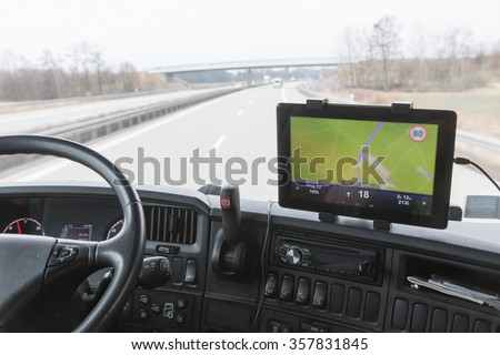 Inside the cab of the truck while driving. Focused on the tablet with navigation. The map is intentionally slightly out of focus. All potential trademarks are removed - stock photo