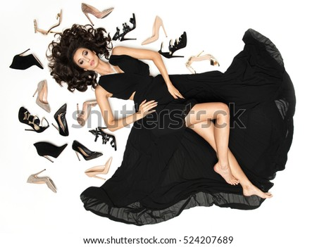 Inside the Studio woman in black dress with gorgeous long dark hair among the shoes.