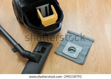 inside Vacuum cleaner and dust bag on the wooden floor - stock photo