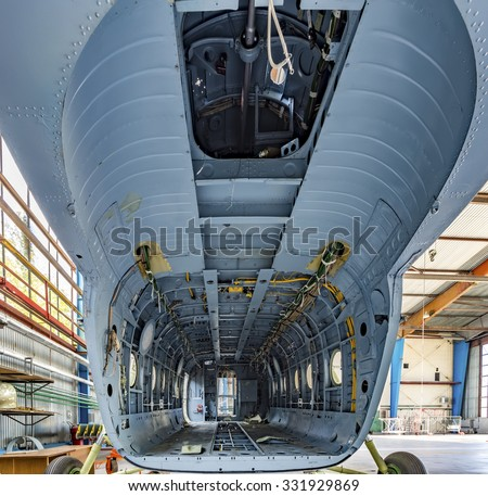 Inside view cargo bay of the helicopter without equipment. Aircraft stand in the hangar.