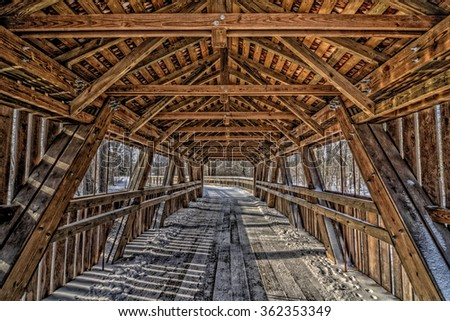 Inside view of a covered bridge in winter with snow and ice on it. Found in Toledo Ohio's Wildwood Metropark. - stock photo