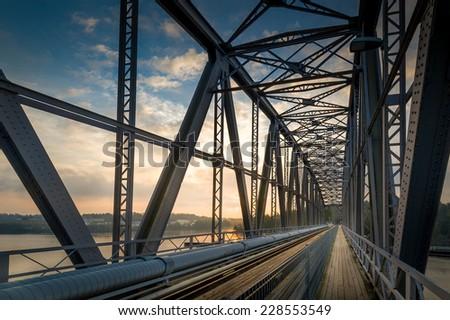 Inside view of big steel railway bridge on sunrise. Savonlinna, Finland - stock photo