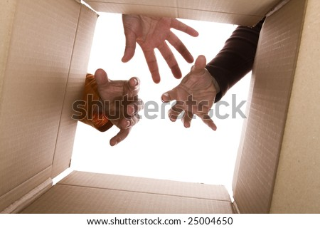 inside view of cardboard box with three hands trying to reach the content (selective focus) - stock photo