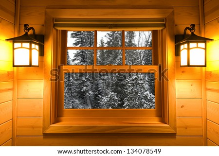 Inside view snow covered trees in a cedar cabin window with lights on - stock photo
