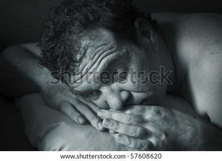 Insomnia. A man tries to fall asleep. Blue tinted - stock photo