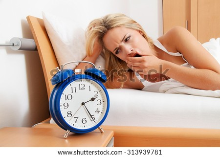insomnia with clock at night. woman can not sleep. - stock photo