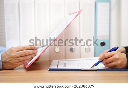 Inspector and auditor are inspecting legal and  financial documents - stock photo