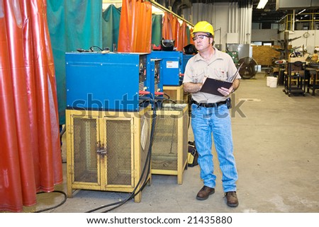 Inspector checking the welding equipment in a metal works factory. - stock photo