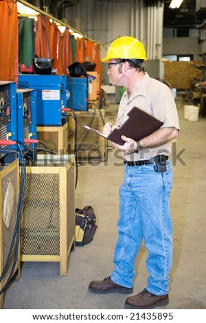Inspector performing a safety Check of welding equipment in a metal work factory. - stock photo