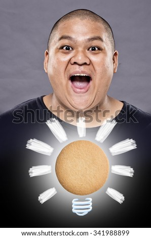 Inspiration concept. A guy have a good idea after eat a cookie. Cookie light bulb metaphor for good idea. - stock photo