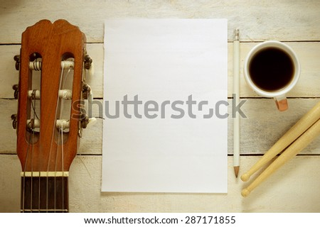 Inspirational background with a Spanish classical guitar on a wooden table while composing. Score sheet, a pencil and a cup of coffee for the music composer, - stock photo