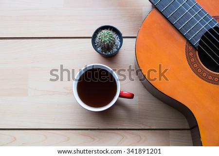 Inspirational background with classical guitar on a wooden table.cup of coffee for the music composer,vintage effect. - stock photo