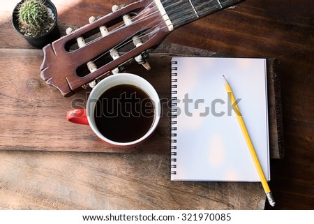 Inspirational background with classical guitar on a wooden table.Score sheet, a pencil and a cup of coffee for the music composer,vintage effect.  - stock photo