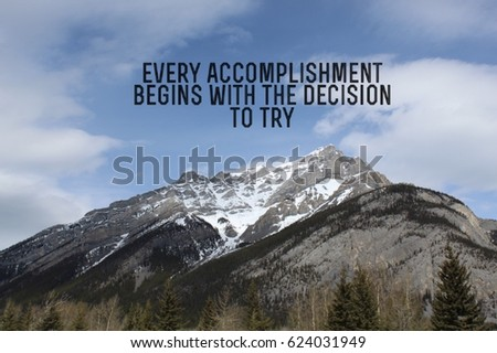 Inspirational black text on blue sky over snow covered mountains.  Evergreen and bare trees in foreground.