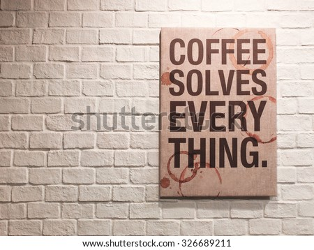 Inspirational motivating quote about coffee on canvas frame hanging on brick wall in the cafe - stock photo